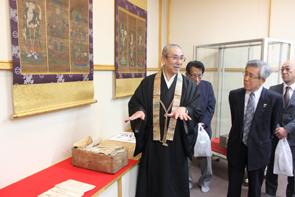 「十二天像」と「観音寺 会式関係文書」の説明をする岩鶴住職(中央)