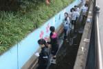 環濠にペンキで絵を描く生徒たち