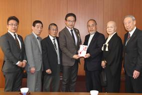 前葉市長に目録を手渡す西田会長(右から3人目)とライブ出演団体の代表者たち