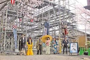 東日寺に建設中の野外舞台の前に並ぶ劇団員たち