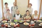 完成した料理の前で…生徒と佐々木さん(前列左から2人目)