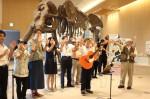 県総合博物館で歌うあつさん(正面)と博物館のスタッフたち
