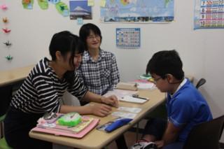 先月のきずな教室で熱心な指導のもと学ぶ子供(右)