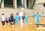 お玉でピンポン玉を運ぶゲームを楽しむ子供たち (緑色の服が聾学校の児童、紺色が倭小学校の児童)
