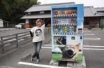 久世さんと、店舗前に設置された寄付型自動販売機