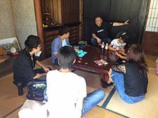 県の事業で三多気の桜を訪れた学生達と話す田中さん(奥)