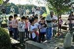 自然教室「里山探検」で山神にお参りする子供達(齋藤正和さん提供)