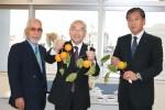 訪問団団長の生川さん(左)より枝付きの柿を贈られ、笑顔の向山町長(中央)と服部教育長
