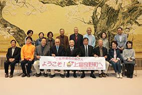 向山町長(前列中央)らと記念撮影をする訪問団