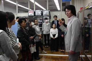 血小板の輸血用血液製剤を手に説明する職員(右)と、学生達