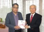 小川実行委員長(右)から松本副理事に寄付