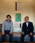 孫の描いた絵を掛軸にした作品の前で宮崎祐史さん(左)と村田義行さん(右)