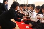 茶道体験で、学生に茶碗の持ち方を教わる園児