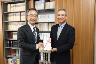間野取締役(左)から井村会長へ寄託金を贈呈