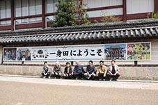 中川さん(左から3人目)らプロジェクトメンバーと、観光客を歓迎する横断幕