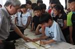 浅生さん(左)に教わり、ヘラで、イラクサ科の植物「からむし」の繊維を引き出す作業に挑戦する児童