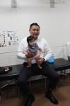 くしもと整形外科で記念撮影する大島親方と、来場した赤ちゃん