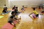 講師の佐田さん(右)の指導で、開脚し体操する参加者たち