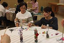 ハーバリウム作りの参加者(左)とアドバイスする奥田常務