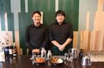 日置さん(左)、渡邊さんとジビエ料理(美杉の木材で改装した壁の前で)