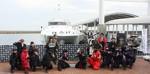 報道発表の儀の津会場で、忍者のステッカーを施した高速船と、忍者隊ら参加者