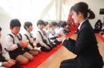 茶道体験で園児(左)に作法を教える学生