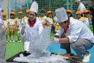 氷の塊からスワンを彫り出している生徒