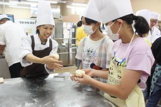 教員(左)の指導でカレーパンの生地をつくる中学生