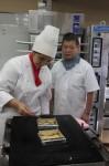 長井さん(右)に焼き方を教わる学生