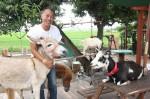 タケガワふれあい動物園で、可愛い動物たちに囲まれる竹川さん