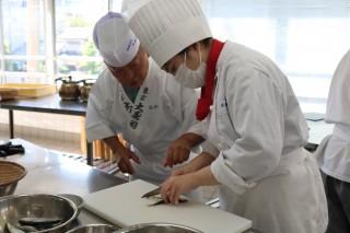 松田さん(左)の指導でイワシをさばく生徒