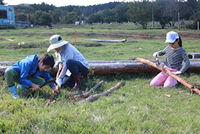 珠の牧で看板の材料をけずる児童たち